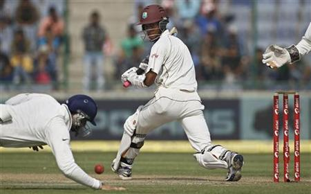 West Indies Kraigg Brathwaite plays a shot as India's VVS Laxman dives to stop the ball during the first day of their first test cricket match in New Delhi November 6, 2011. REUTERS/Adnan Abidi