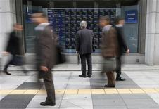 <p>A man looks at an electronic board displaying stock prices outside a brokerage in Tokyo November 10, 2011. REUTERS/Toru Hanai</p>