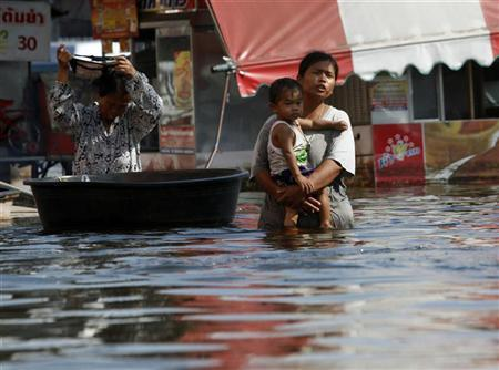 A woman carries her son as she wades through a flooded street in Nonthaburi province, on the outskirts of Bangkok November 16, 2011. REUTERS/Chaiwat Subprasom (THAILAND - Tags: ENVIRONMENT DISASTER SOCIETY)