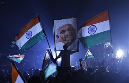 A supporter of veteran Indian social activist Anna Hazare holds his portrait on the ninth day of Hazare's fast at Ramlila grounds in New Delhi August 24, 2011. REUTERS/Adnan Abidi