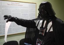 <p>A local resident dressed as the Star Wars Darth Vader shows papers as he visits the mayor's office in Odessa November 14, 2011. An Odessite dressed as the Star Wars villain visited the mayor's office this week to claim a free land plot citing Ukrainian legislation which grants every citizen the right to own 1,000 square metres of land. Picture taken November 14, 2011. REUTERS/Stringer</p>