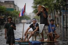 <p>A man pulls a makeshift raft carrying his friends and with a Thai national flag attached as they make their way through the newly flooded neighborhood in Bangkok's suburbs November 11, 2011. REUTERS/Damir Sagolj</p>