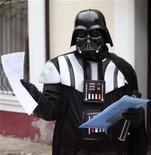 <p>Un residente local vestido como Darth Vader muestra una serie de papeles en los alrededores de la oficina del alcalde en Odesa, Ucrania, nov 14 2011. Saludando el ingreso de las autoridades locales en el lado oscuro, Darth Vader ha pedido un terreno en el puerto ucraniano de Odessa, en el Mar Negro, para poder aparcar su nave espacial. REUTERS/Stringer</p>