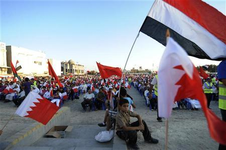 A boy sits between Bahraini (front L and R) flags as he attends an anti-government gathering organised by Bahrain's main opposition party Al Wefaq in Budaiya, west of Manama, October 29, 2011. REUTERS/Hamad I Mohammed