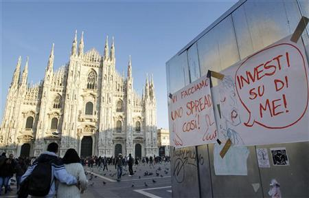 Signs that read ''So we make a spread'' (L) and ''Invest on me'' are pictured in Duomo Square in downtown Milan November 23, 2011. REUTERS/Alessandro Garofalo