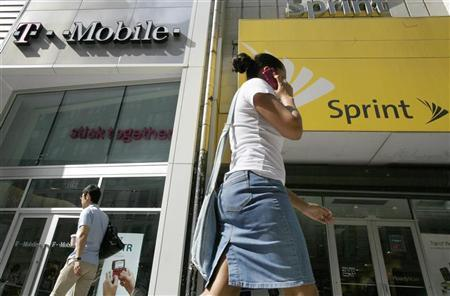 A woman talks on her phone as she walks past T-mobile and Sprint wireless stores in New York July 30, 2009. REUTERS/Brendan McDermid