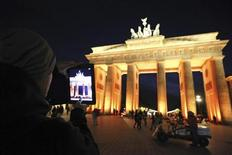 <p>A man takes a picture with his iPad of the Brandenburg Gate as it is illuminated during the Festival of Lights in Berlin October 12, 2011. REUTERS/Fabrizio Bensch</p>