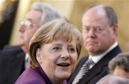 Former German Finance Minister Peer Steinbrueck (R) watches German Chancellor Angela Merkel (C) as she arrives with Dieter Hundt (L), head of Confederation of German Employers' Association (BDA) to the annual association's meeting in Berlin, November 22, 2011. REUTERS/Fabrizio Bensch