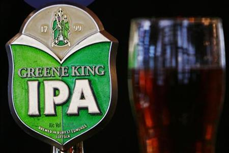 A Greene King beer pump and pint of beer are seen in a pub in central London July 2, 2008. REUTERS/Luke MacGregor