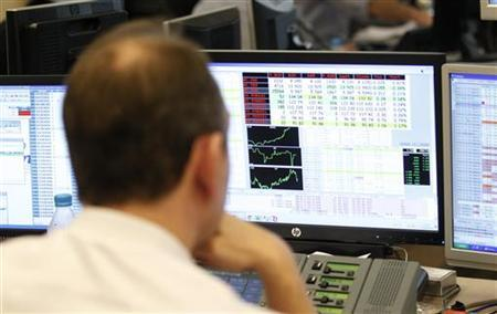 A broker looks at trading screens at a brokers' office in Madrid December 1, 2011. REUTERS/Andrea Comas
