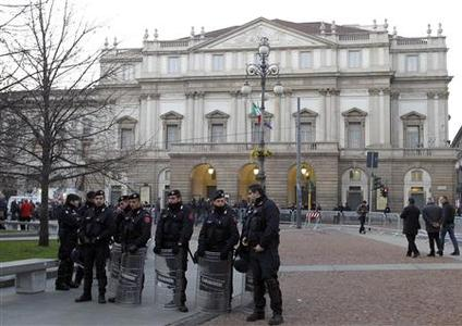 Carabinieri policemen stand in front of La Scala opera house in Milan December 7, 2011. Mozart's ''Don Giovanni'', conducted by director Daniel Barenboim , will open for the 2011 opera season at the La Scala opera house. REUTERS/Alessandro Garofalo