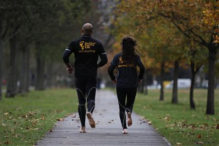 David Robinson (L) and Anna Toombs run barefoot in a park in south London December 1, 2011. REUTERS/Stefan Wermuth
