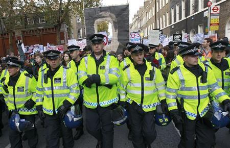Police officers walk ahead of demonstrators at the beginning of a protest march in central London November 9, 2011. REUTERS/Suzanne Plunkett
