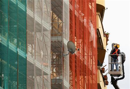 Workers are seen on a crane as they work next to a building in Rome December 9, 2011. REUTERS/Alessandro Bianchi