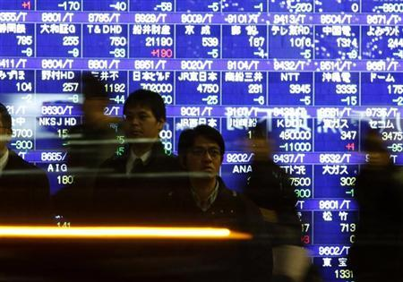 Passers-by walk in front of a stock quotation board in Tokyo December 9, 2011. REUTERS/Issei Kato