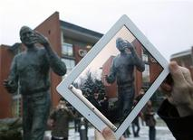 <p>A man takes pictures with his iPad during the unveiling ceremony of a statue of the late Apple co-founder Steve Jobs at a private business park in Budapest December 21, 2011. REUTERS/Laszlo Balogh</p>