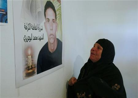 Mannoubia Bouazizi, mother of Mohamed Bouazizi, looks at a picture of her son at her home in the Tunisian town of Sidi Bouzid, 265 km (165 miles) south of Tunis February 6, 2011. REUTERS/Louafi Larbi