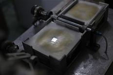 <p>A piece of silver is seen on a machine before it is turned into silver paper at a factory in New Delhi December 15, 2011. Silver prices, which averaged under 18,000 rupees per kilo in the five years to 2009, hit a peak of 73,600 rupees in April, and futures still trade around 53,000 rupees. India, the world's largest importer of silver, bought 3,029 tonnes in 2010, double the year earlier after a weak monsoon cut demand in 2009. Picture taken December 15, 2011. REUTERS/Adnan Abidi</p>