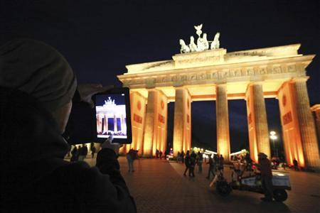 A man takes a picture with his iPad of the Brandenburg Gate as it is illuminated during the Festival of Lights in Berlin October 12, 2011. REUTERS/Fabrizio Bensch