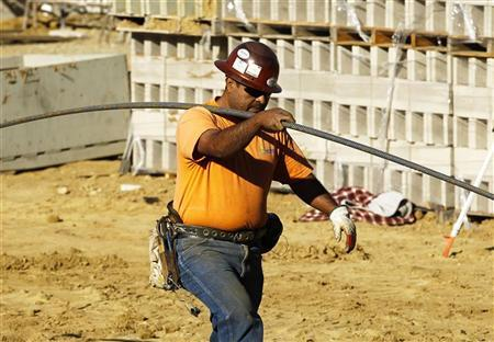 A construction worker carries materials on the job building a shopping center complex in Solana Beach, California January 6, 2012. REUTERS/Mike Blake