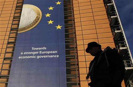 A banner featuring a Euro coin is seen on the European Commission headquarters building in Brussels December 19, 2011. REUTERS/Yves Herman