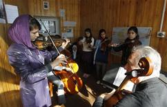 <p>A teacher watches a female student playing the violin at the Kabul Music Academy January 7, 2012. In Afghanistan's sole music academy, students learn how to play traditional and western instruments as part of a government initiative to relieve the pains of decades of war through music. Despite a rich musical legacy, Afghanistan's melodic development has been severely disrupted by years of war and outright banned during the austere rule of the Taliban. At the Afghanistan National Institute of Music, orphans learn how to sing and play instruments alongside talented promising musicians who are selected on merit. Picture taken January 7, 2012. REUTERS/Omar Sobhani</p>