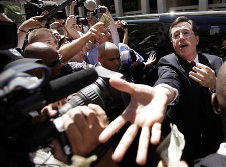Stephen Colbert (R) accepts one dollar contributions outside the Federal Election Commission (FEC) after his meeting to discuss his proposal to establish an Independent expenditure-only political committee and Draft Advisory Opinion 2011-12 in Washington June 30, 2011. REUTERS/Yuri Gripas