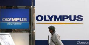 <p>A man walks past signboards of Olympus Corp outside its showroom in Tokyo January 12, 2012. REUTERS/Toru Hanai</p>