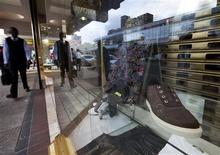 <p>A man walks past a shop window displaying designer clothes on a Durban street, January 17, 2012. REUTERS/Rogan Ward</p>