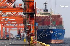 <p>Workers load a container onto a cargo ship at a port in Tokyo August 15, 2011. REUTERS/Issei Kato</p>