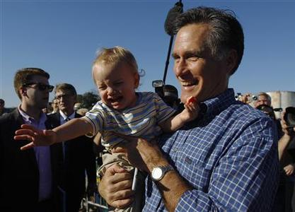 Republican presidential candidate and former Massachusetts Governor Mitt Romney returns a baby to his mother in the audience at a campaign rally at Eastern Shipbuilding Group in Panama City, Florida January 28, 2012. REUTERS/Brian Snyder