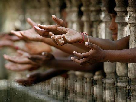 フェンス越しに手を伸ばすホームレスの子どもたち(2006年9月27日、インド・シリグリ)