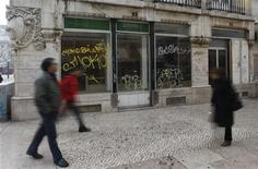 <p>People walk near a closed down shop in downtown Lisbon January 26, 2012. REUTERS/Rafael Marchante</p>