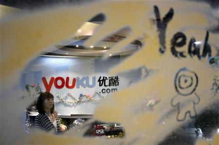 An employee is seen through a glass wall as she walks past the logo of Youku.com above the reception desk at the company's headquarters in Beijing, December 9, 2010. REUTERS/Soo Hoo Zheyang