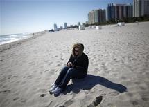 <p>A tourist wearing a jacket sit at the beach in South Beach Miami, Florida January 11, 2010. REUTERS/Carlos Barria</p>