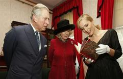 <p>Actress Gillian Anderson (R) shows a first edition of a Charles Dickens book, with the author's annotations, to Britain's Prince Charles and his wife Camilla, Duchess of Cornwall, during a tour of the Dickens Museum in London February 7, 2012. Tuesday marked the 200th anniversary of Charles Dickens' birth. REUTERS/Andrew Winning</p>