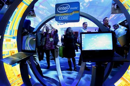 A woman takes a photo of ultrabooks at the Intel booth during the 2012 International Consumer Electronics Show (CES) in Las Vegas, Nevada January 10, 2012. REUTERS/Steve Marcus