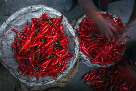 A worker sorts out chillies for sale at Delhi's Azadpur Mandi February 10, 2012. REUTERS/Parivartan Sharma
