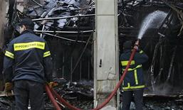 <p>Firemen hose down a burned-out shop after a night of violence which followed the Greek parliament approval of a deeply unpopular austerity bill in Athens, February 13, 2012. REUTERS/John Kolesidis</p>