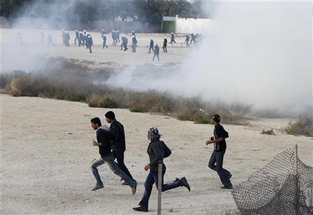 Anti-government protesters run as tear gas is fired by riot police after protesters broke through barriers to advance towards Farooq Junction formerly known as Pearl Square in Budaiya west of Manama, February 13, 2012. REUTERS/Hamad I Mohammed