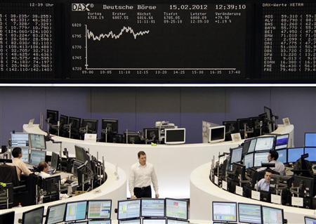 Traders are pictured at their desks in front of the DAX board at the Frankfurt stock exchange February 15, 2012. REUTERS/Remote/Amanda Andersen