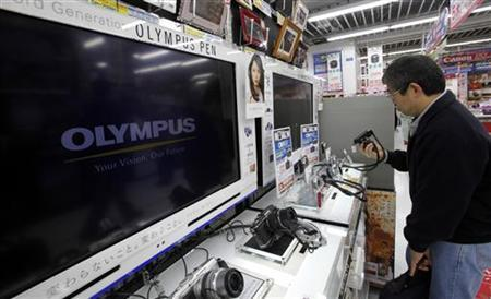 A man looks at Olympus Corp digital cameras at an electronics store in Tokyo February 13, 2012. REUTERS/Yuriko Nakao