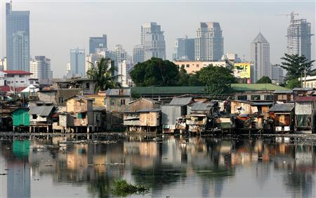 Slums are seen along a river with the skyline of Makati, Manila's financial district, in the background in this June 16, 2006 file photo. REUTERS/Cheryl Ravelo/Files