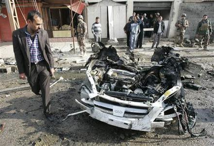A man walks past the remains of a vehicle used in a bomb attack in Kirkuk, 250 km (155 miles) north of Baghdad February 23, 2012. REUTERS/Ako Rasheed