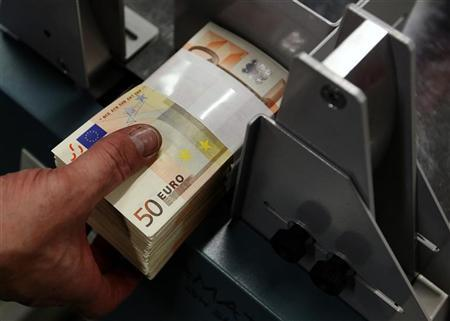 An employee at the Belgian Central Bank adjusts fifty-euro notes with a machine in Brussels December 8, 2011. REUTERS/Yves Herman