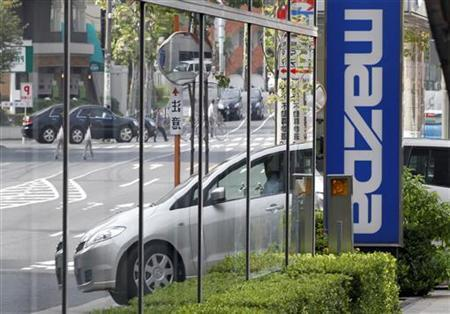 A Mazda car is reflected in a Mazda dealership in Tokyo October 18, 2010. Shares of Mazda Motor Corp slipped on Monday after news at the weekend that top shareholder Ford Motor Co plans to sell almost all of its remaining stake in the Japanese automaker it once controlled. REUTERS/Toru Hanai