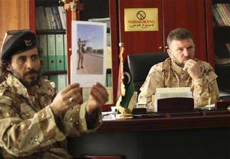 Faraj al-Swehli (R), commander of the Swehli Brigade, speaks during an interview with Reuters in Tripoli March 7, 2012 . Two British journalists held in Libya on suspicion of spying have their own room, access to telephones and are fed meals of chicken and pasta, but they will be kept where they are for several more weeks, the head of the militia holding them said. REUTERS/Ismail Zitouny