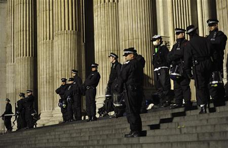 Riot police stand guard as they prepare to remove protesters from the Occupy encampment on the steps of St Paul's Cathedral in London February 28, 2012. REUTERS/Dylan Martinez