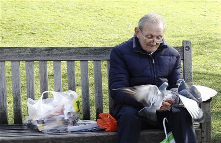 An elderly man feeds pigeons in St James's Park in London March 8, 2012. REUTERS/Luke MacGregor