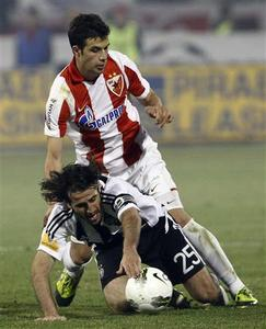 Red Star's Luka Milivojevic (R) fights for the ball with Partizan's Stefan Babovic during their Serbia's national cup semi-final in Belgrade March 21, 2012. REUTERS/Ivan Milutinovic